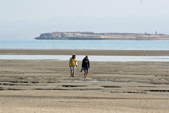 two people walking across the tide area