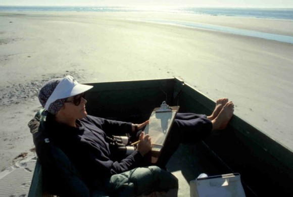 Woman sitting in box on a beach with a clipboard