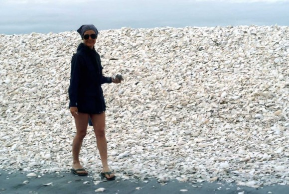 Woman walking amongst a hill of sea shells