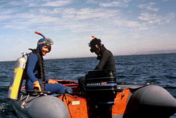 Two scientists with scuba gear sitting on edges of boat.